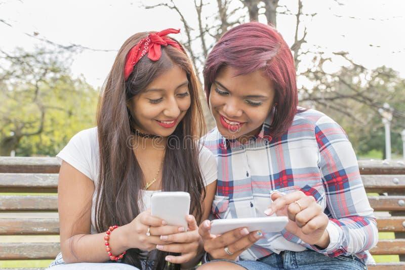 Två le kvinnavänner som använder den smarta telefonen royaltyfri fotografi