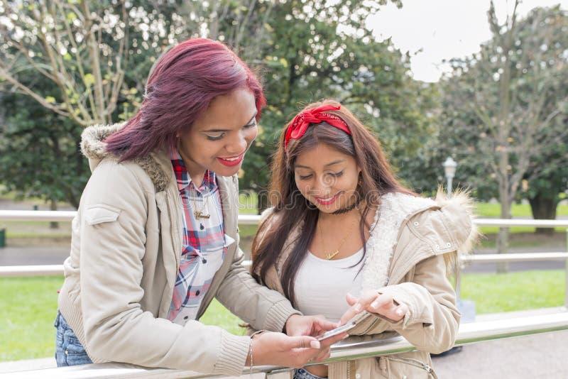 Två le kvinnavänner som delar socialt massmedia i en smart telefon royaltyfria bilder