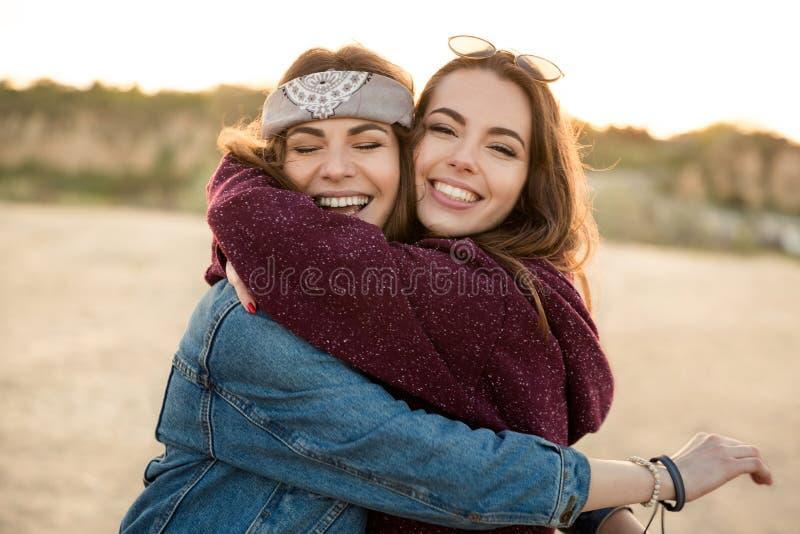 Två le kvinnliga vänner som kramar sig royaltyfria bilder