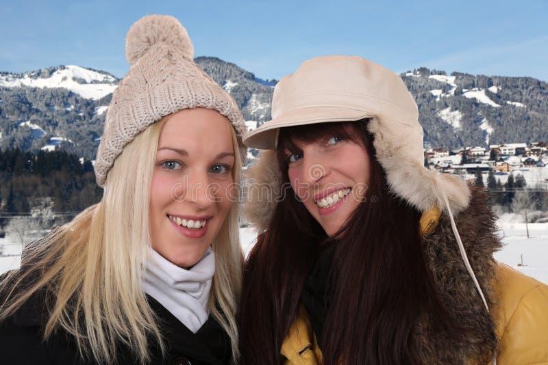 Två le kvinnor på vinterferier i bergen royaltyfri bild