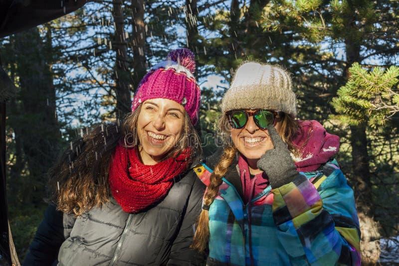 Två le kvinnor som bär varm kläder i en solig vinterdag arkivfoton