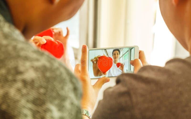 Två le röda hjärtor som rymms, genom att le kvinnliga händer för sjuksköterska` s arkivfoto