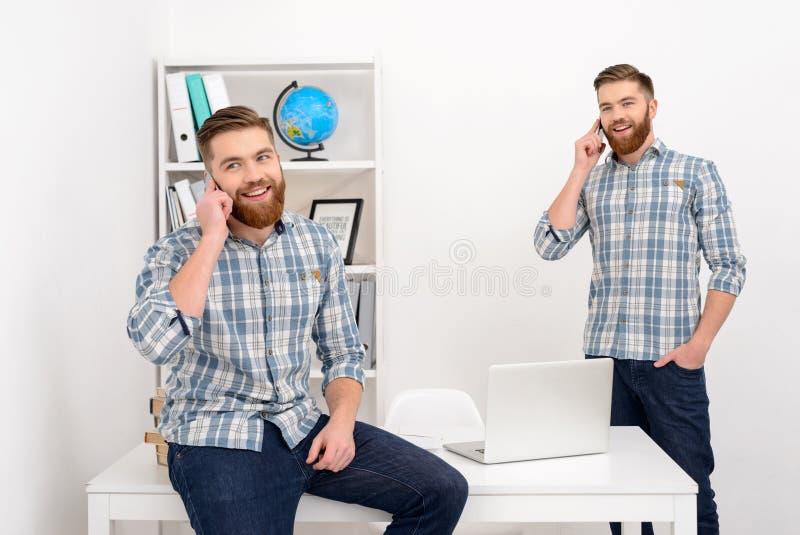 Två le tillfälliga klon för affärsmän som talar på mobiltelefonen royaltyfria bilder