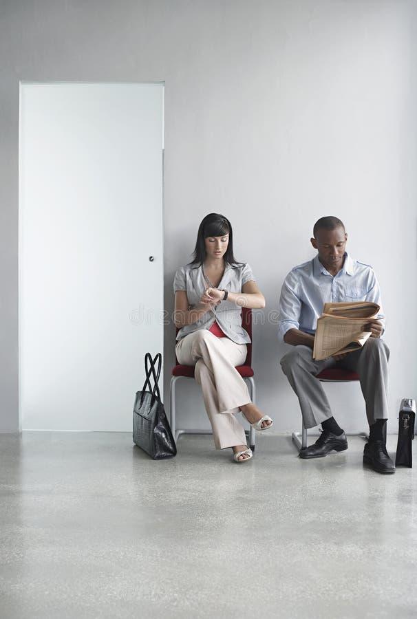 Två ledare som sitter på stolar i korridor arkivbild