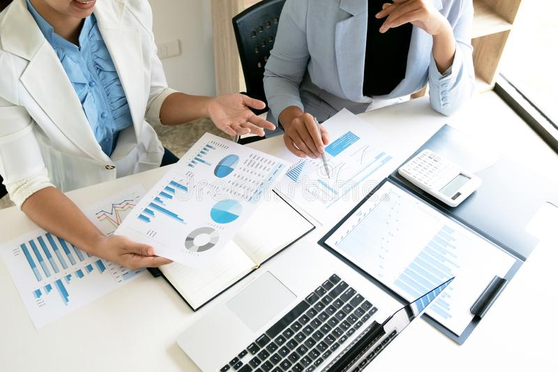 Två ledareaffärskvinnor som diskuterar diagrammen och graferna som visar resultaten arkivbild