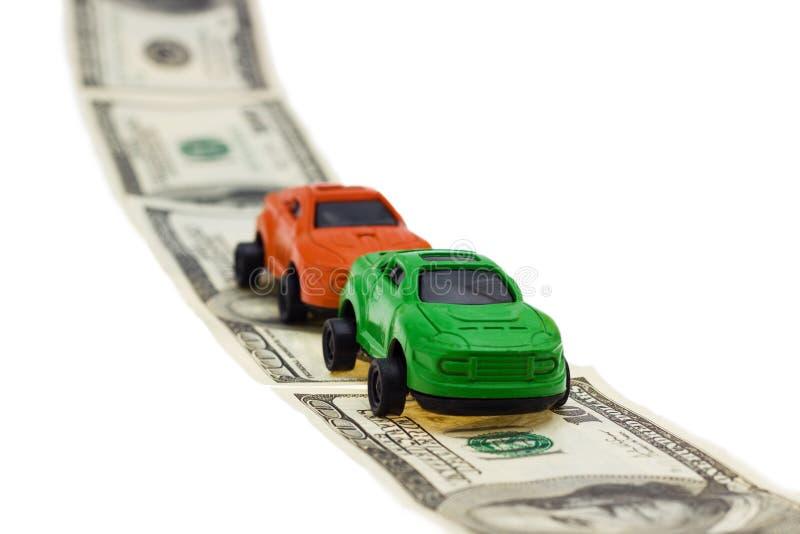 Två leksakbilar på pengarvägen på vit bakgrund arkivfoton