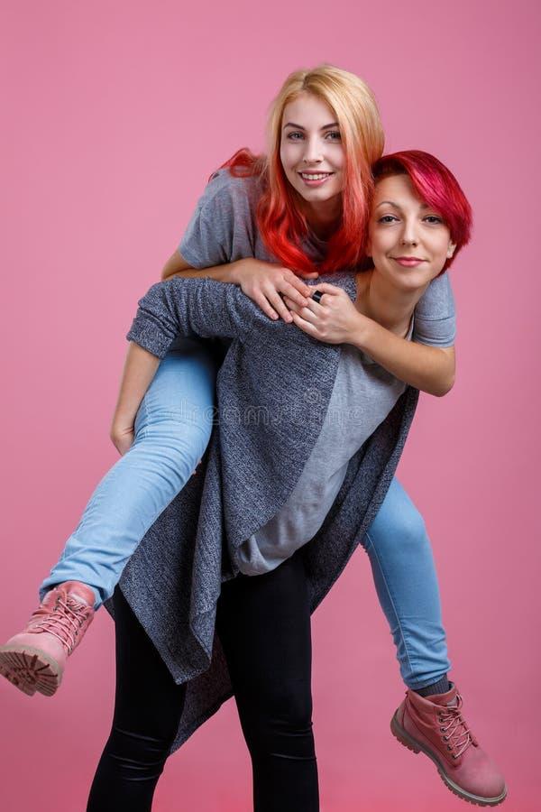 Två lesbiska flickor, en lyftte andra på baksidan På en rosa bakgrund arkivfoton
