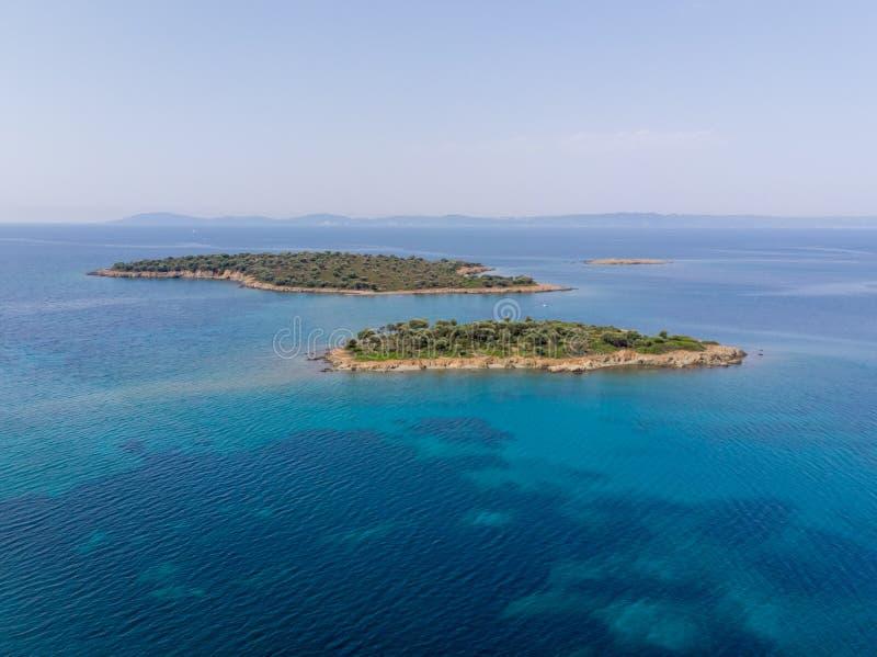 Två lilla öar som omges med blått havsvatten med berg i bakgrund Flyg- sikt för surr arkivfoton