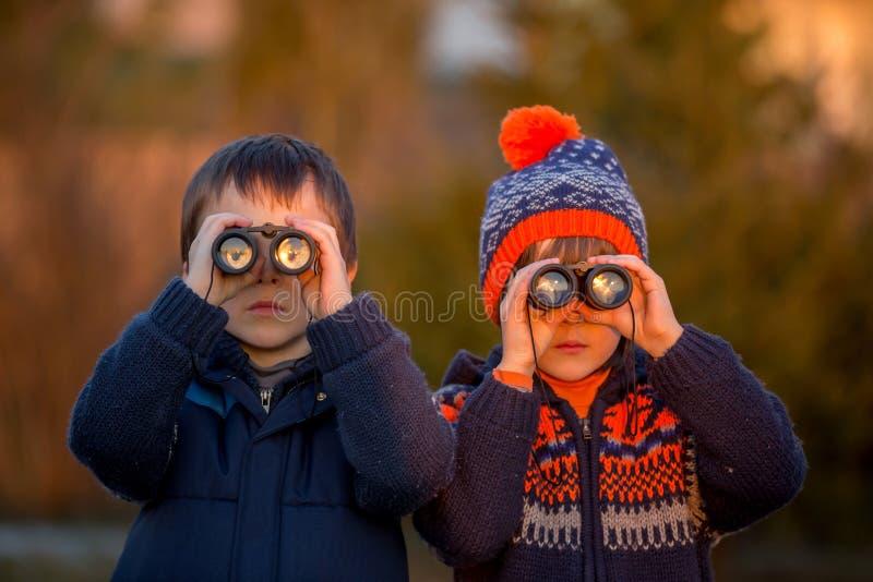 Två lilla barn, pojkar, undersökande natur med kikare arkivbilder