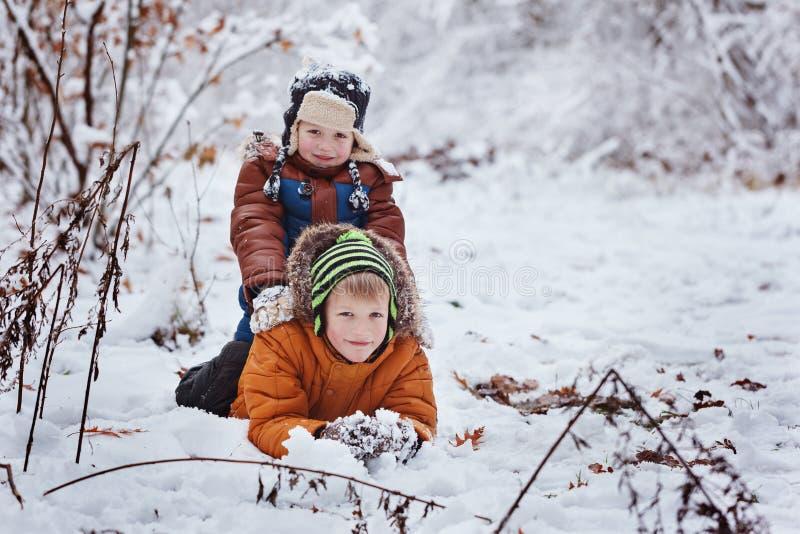Två lilla barn, pojkebröder som utomhus spelar och ligger i snö under snöfall Aktiv fritid med barn i vinter på Co royaltyfri foto