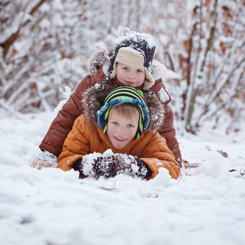 Två lilla barn, pojkebröder som utomhus spelar och ligger i snö under snöfall Aktiv fritid med barn i vinter på Co arkivfoto