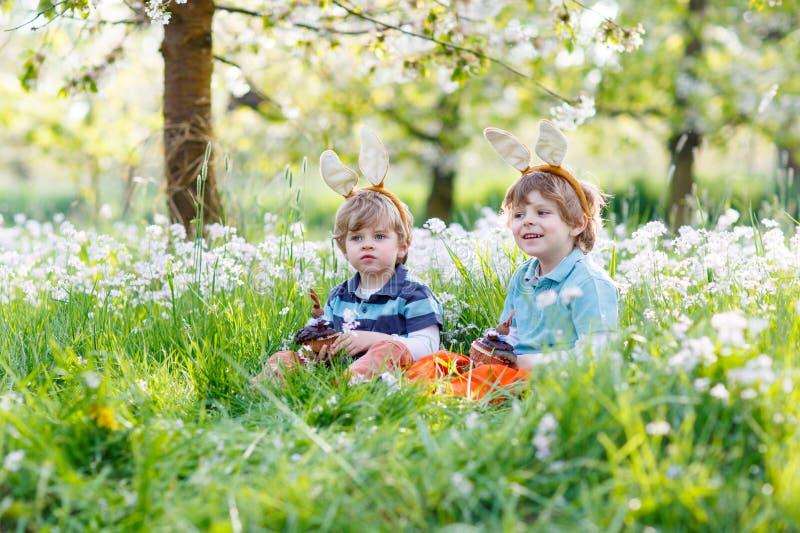 Två lilla barn som bär öron för påskkanin och äter chocola arkivbilder