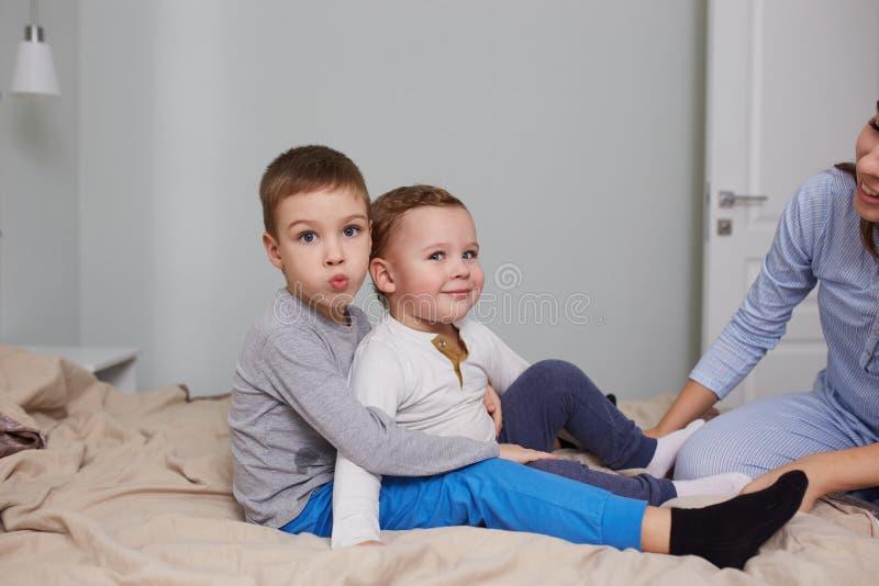 Två lilla bröder sitter huging på sängen med den beigea filten i det ljusa hemtrevliga sovrummet royaltyfri bild