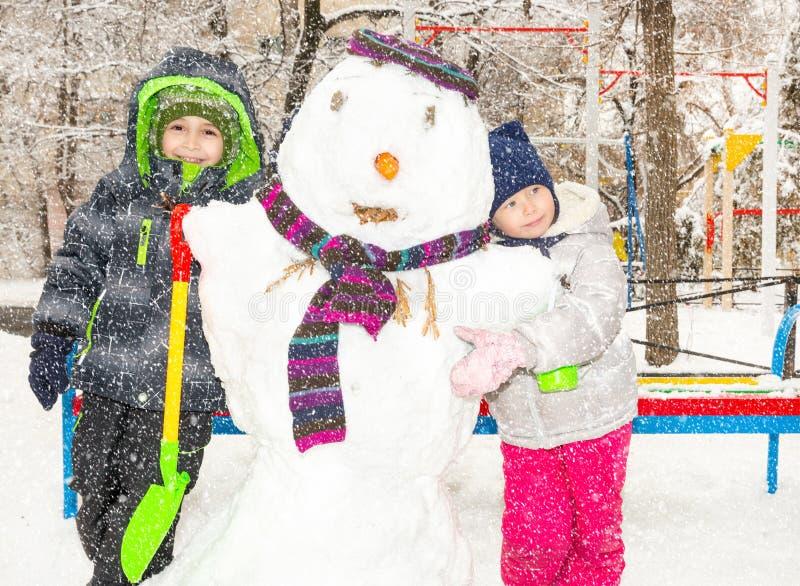 Två lilla djävuler, ungar som gör en snögubbe, spelar och har gyckel med snö som är utomhus- på kall dag Aktiv det friafritid med arkivbild