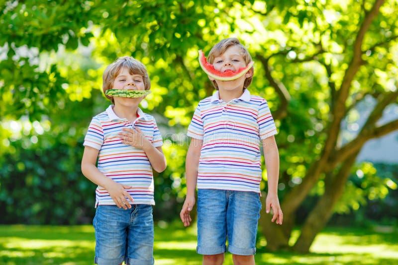 Två lilla förskole- ungepojkar som äter vattenmelon i sommar royaltyfri fotografi