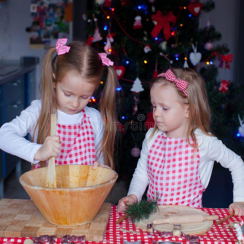 Två lilla förtjusande flickor gör pepparkakakakor arkivfoton