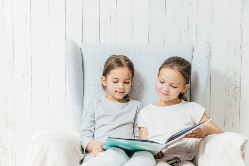 Två lilla förtjusande systrar sitter i soffa, läste att intressera boken, fotografering för bildbyråer