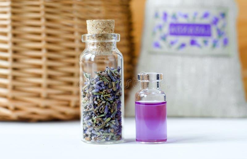 Två lilla flaskor med torra lavendelknoppar och aromoljadoft, tinktur, extrakt, avkok Aromatherapyingredienser royaltyfria foton