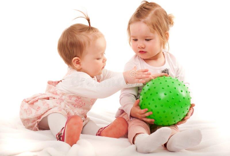 Två lilla flickor som spelar med bollen royaltyfria foton