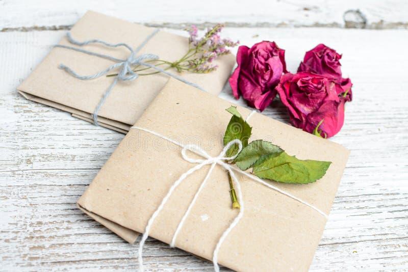 Två lilla gåvor som slås in i ecologic papper, gammal trävit tabell royaltyfria foton