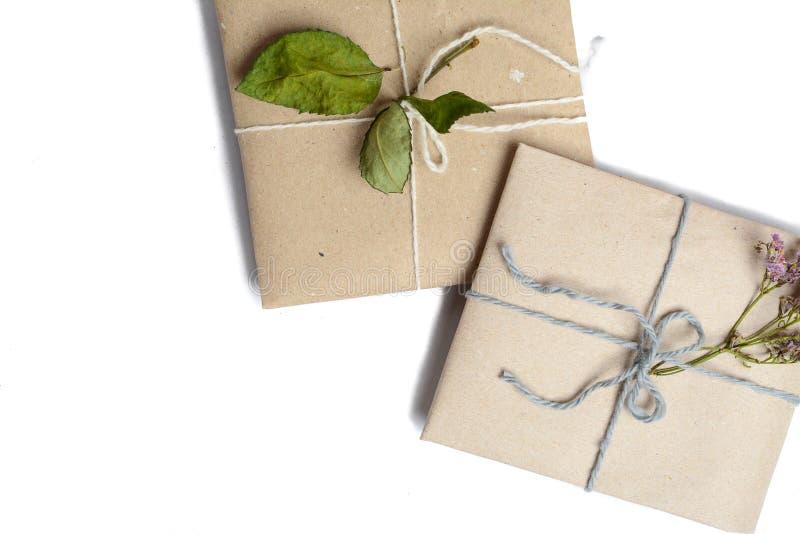 Två lilla gåvor som slås in i ecologic papper, vitt som isoleras med utrymme för texthandstil fotografering för bildbyråer