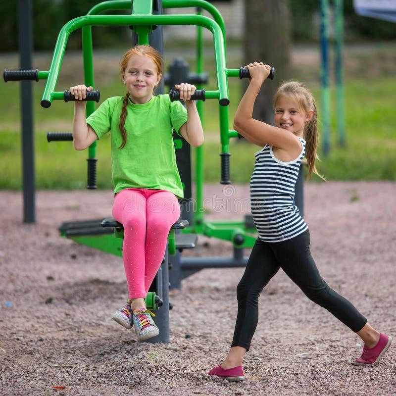 Två lilla gladlynta flickor är förlovade i sportkonditionutrustning på lekplatsen royaltyfri bild