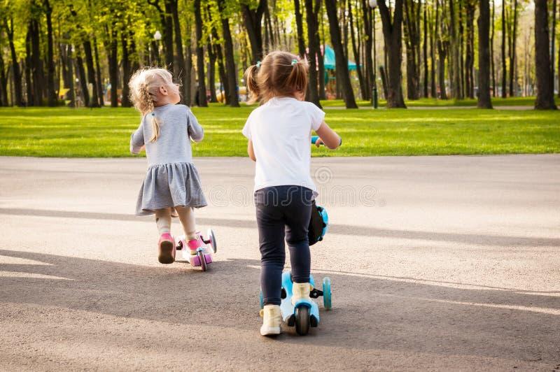 Två lilla gulliga flickor rider deras sparkcyklar royaltyfri bild