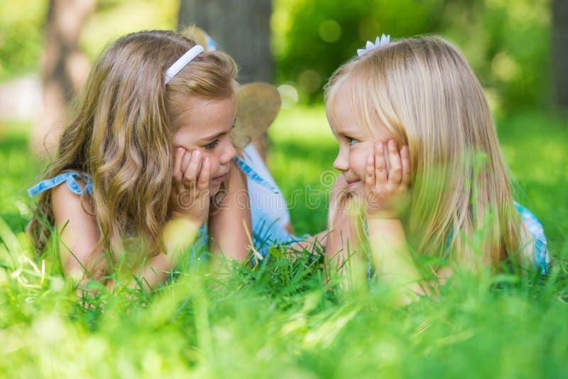 Två lilla gulliga flickor som ligger på gräsmatta royaltyfri fotografi