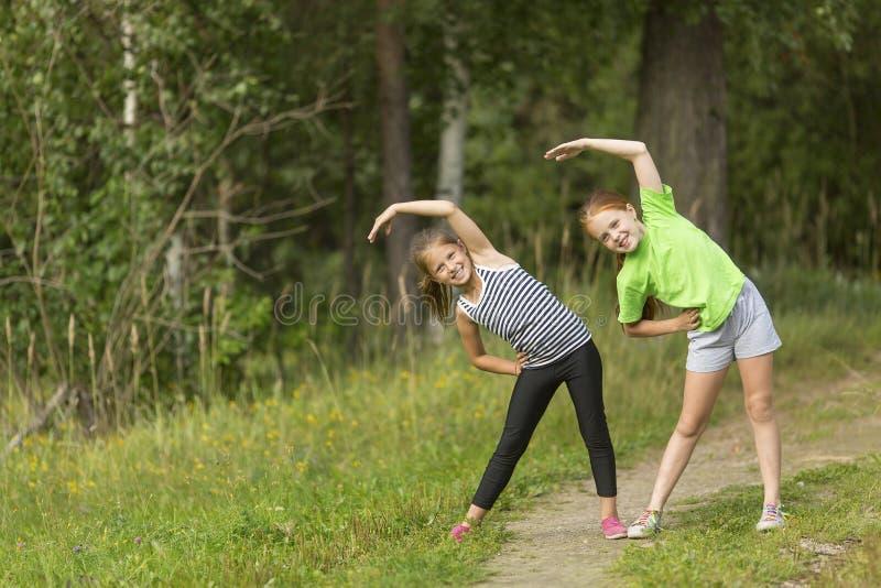 Två lilla gulliga flickor som utomhus värmer upp royaltyfri fotografi