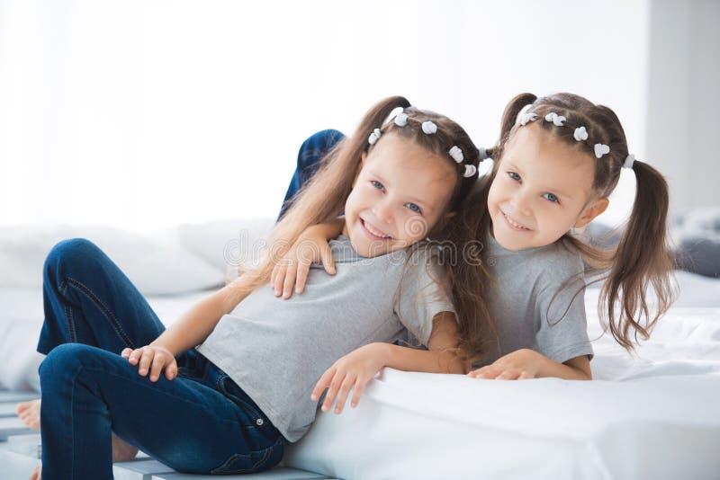 Två lilla gulliga le flickor som systrar kopplar samman, sitter på sängen i rummet royaltyfri foto