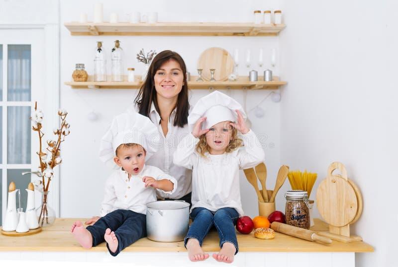 Två lilla kockar som sittting på tabellen i köket med modern arkivfoto