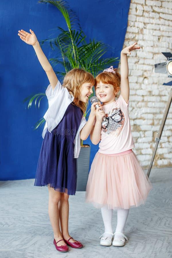 Två lilla le ungar dansar och sjunger en sång i karaoke Co fotografering för bildbyråer