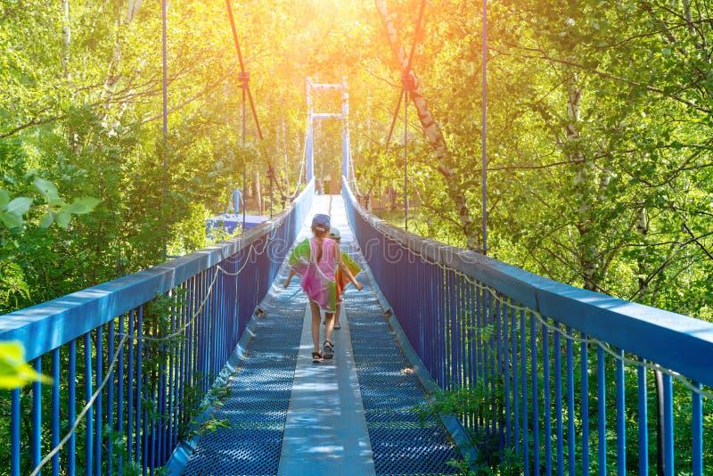 Två lilla lyckliga flickor promenerar en hängande bro på en solig dag royaltyfri foto