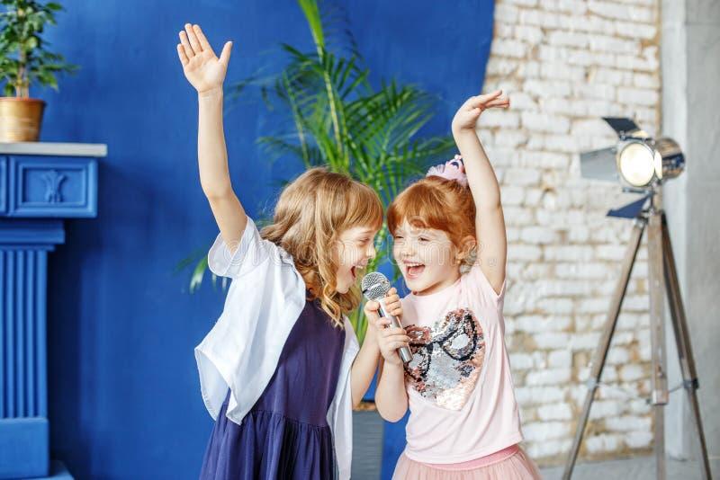 Två lilla roliga barn dansar och sjunger en sång i karaoke _ arkivbilder