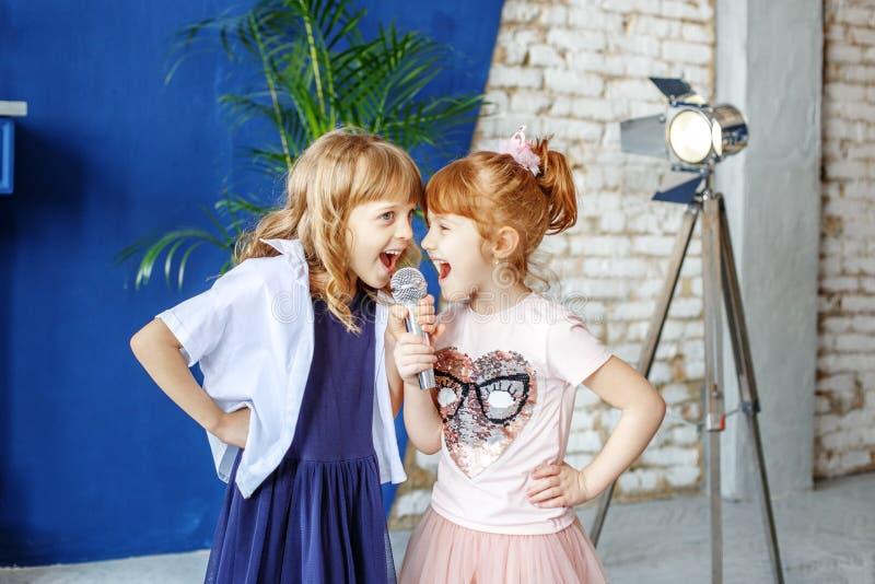 Två lilla roliga barn sjunger en sång i en mikrofon grupp Th royaltyfria bilder