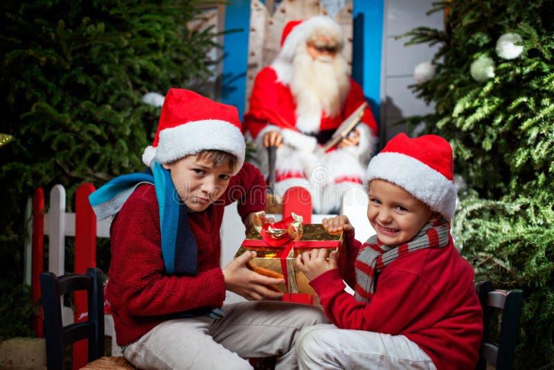 Två lilla Santa Clauses som strider en gåva royaltyfria bilder
