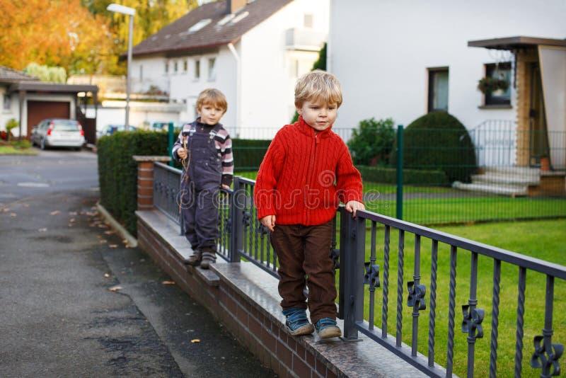 Två lilla siblingpojkar som går på stadsgatan. royaltyfri foto