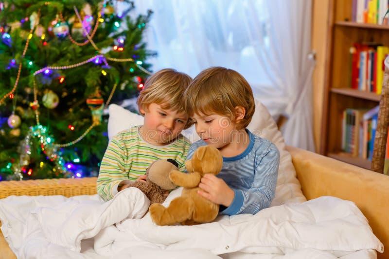 Två lilla siblingpojkar som spelar leksaker på jul royaltyfria foton