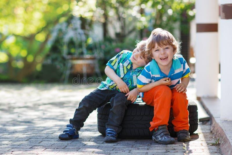 Två lilla siblingpojkar som utomhus kramar och har roligt fotografering för bildbyråer