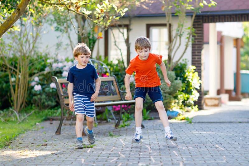 Två lilla skola- och förträningsungepojkar som hoppar hage på lekplats arkivfoto