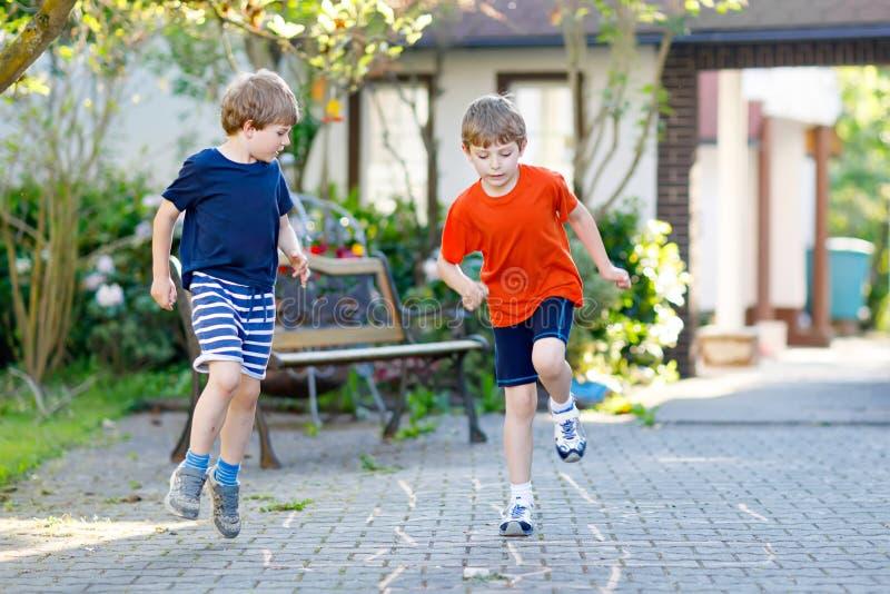 Två lilla skola- och förträningsungepojkar som hoppar hage på lekplats arkivbilder