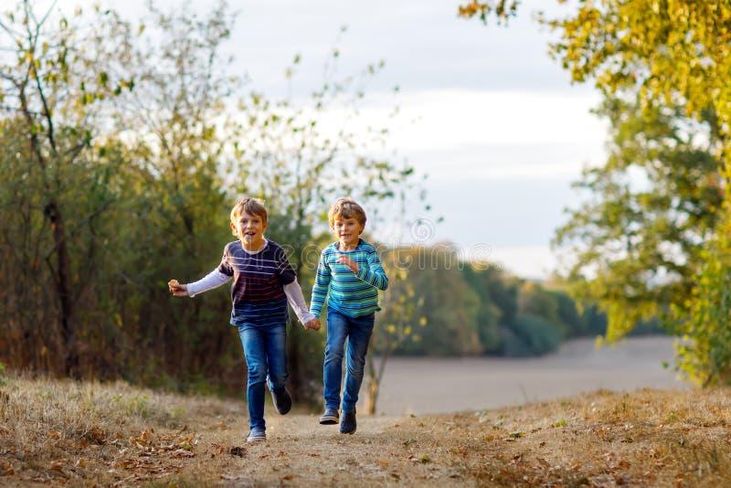 Två lilla skolaungepojkar som kör och hoppar i barn, bästa vän och syskon för skog som lyckliga har gyckel på varmt arkivbilder