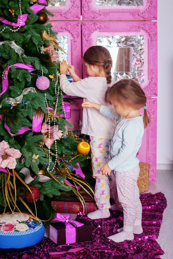Två lilla systrar i pyjamas dekorerade julgranen Christma royaltyfria foton