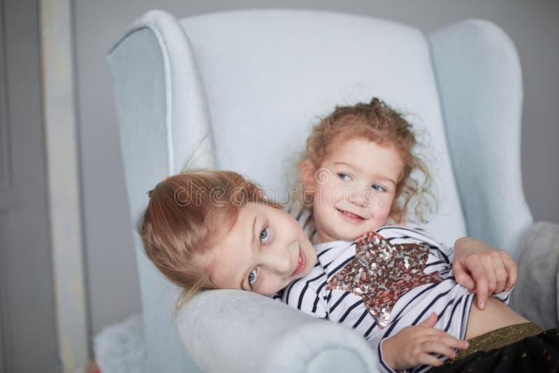 Två lilla systrar i pyjamas som sitter i en stol royaltyfria bilder