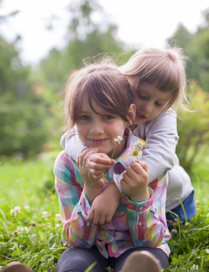 Två lilla systrar i sommardag arkivfoton