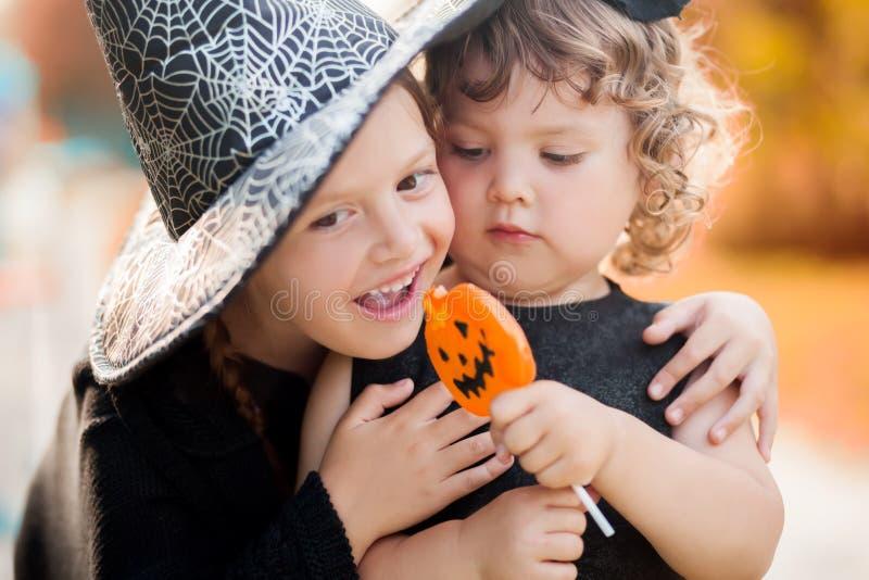 Två lilla systrar klädde som häxor, trick eller fest royaltyfri bild