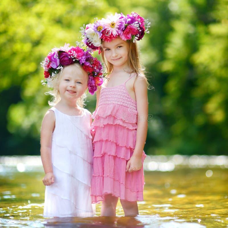 Två lilla systrar som bär blommakronor royaltyfria foton