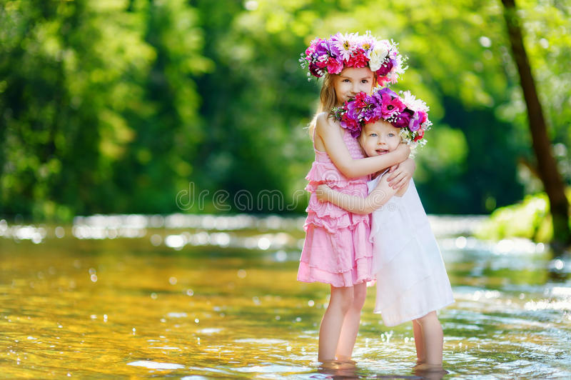 Två lilla systrar som bär blommakronor royaltyfria bilder