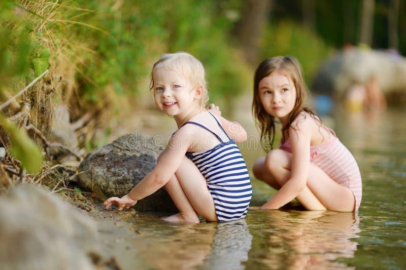 Två lilla systrar som har gyckel i en flod royaltyfria foton