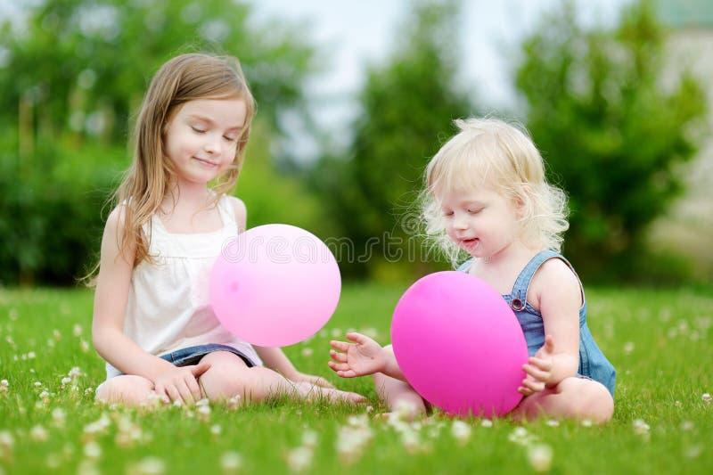 Två lilla systrar som har gyckel med rosa ballonger arkivbilder